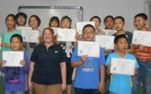 Kelly with students and diploma-350